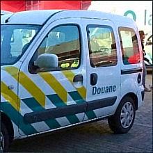 Foto van een auto waarop het woord 'douane' valt te lezen. Onderschrift foto: 'Het woord 'diwaan' belandde als 'divan' en als 'douane' in onze taal. (Fotobron: flickr.com)'
