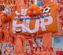 Foto van de gevel van een Nederlandse huis; de gevel is versierd met oranje spullen; de foto zal genomen zijn tijdens een groot internationaal voetbaltoernooi waaraan het Nederlands voetbalelftal deelnam. Onderschrift foto: 'Oranje: het begon allemaal met een sinaasappel. (Fotobron: flickr.com)'