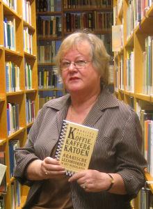 """Foto van Marlies Philippa, die haar boek 'Koffie, kaffer en katoen'  toont. Onderschrift foto: 'Marlies Philippa: """"Niet de Arabieren hebben de nul ontdekt, maar de Indiërs.""""'"""